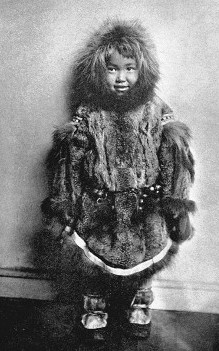Inuit child wearing a  fur parka and mukluk boots